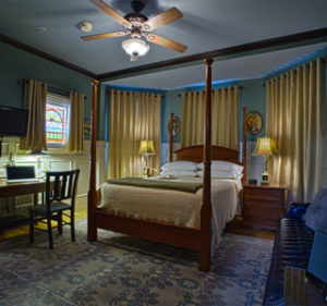 Room 205 showing antique poster bed and stained glass window