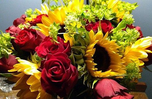Lovely bouquet of red roses, large yellow sunflowers and greenery.