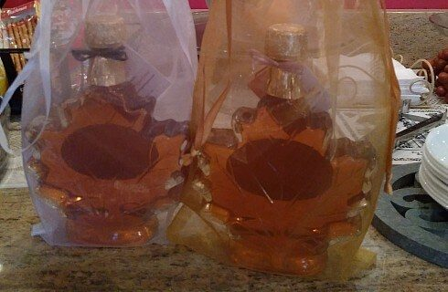 Two glass bottles of syrup in the shape of maple leaves inside fabric gift bags.
