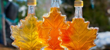 3 bottles in maple leaf shape filled with an amber colored liquid
