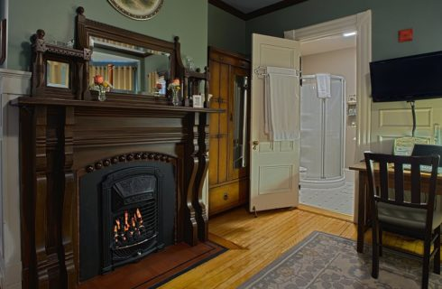 Beautiful dark brown wood mantle around a lit fireplace next to a sitting desk and an open door leading to a bathroom.