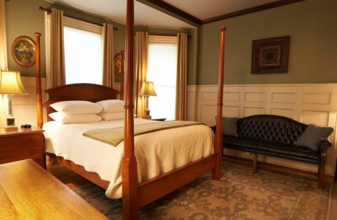 Large bedroom with wooden four poster bed, large rug, board and batten on walls and a leather couch