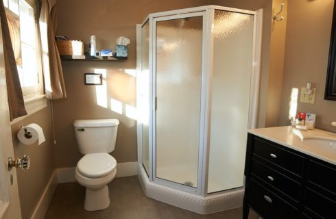 Bathroom with beige walls, black and white vanity, toilet and corner stand up shower.