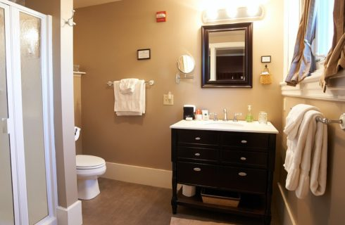 Bathroom with black and white vanity, white toilet, white towels on silver racks, and stand up shower.