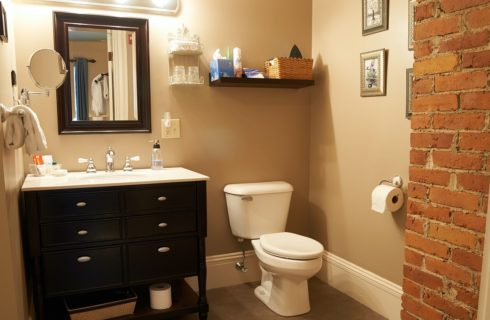 Bathroom with rectangular mirror over black and white vanity, white toilet and red brick corner feature.
