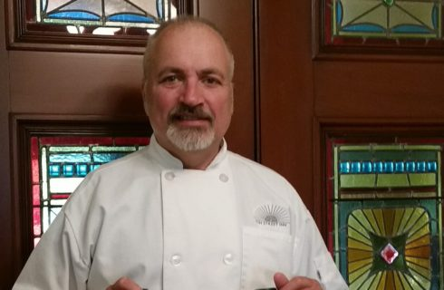 Man in a white chef's coat standing in front of large brown doors with colorful stained glass windows.