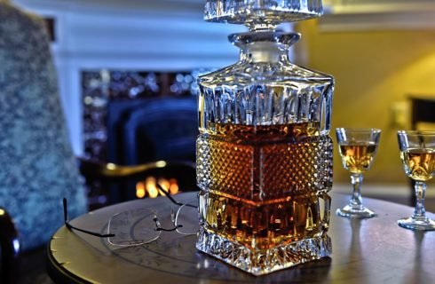 Large decorative glass container full of brandy on a circular table with two small glasses of brandy.