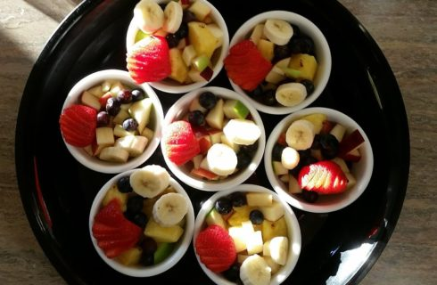 Seven small round white bowls full of cut up fruit on a round black plate.