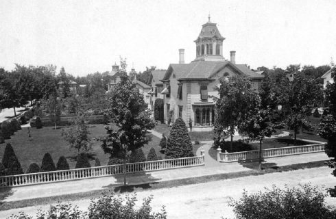 Black and white historical image showing stately home in a large lot with many trees and white fence