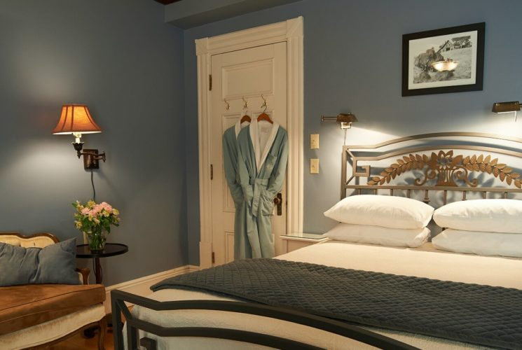 Bedroom with light blue walls, bed with white linens and iron frame, white tufted couch and two robes hanging on the door.