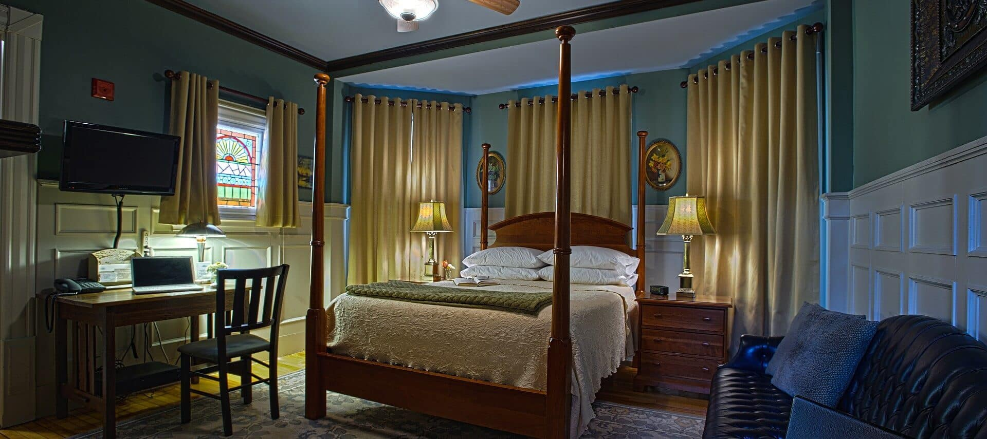 Large four poster bed with white linens in a room with many windows covered in curtains, board and batten walls and black leather couch.