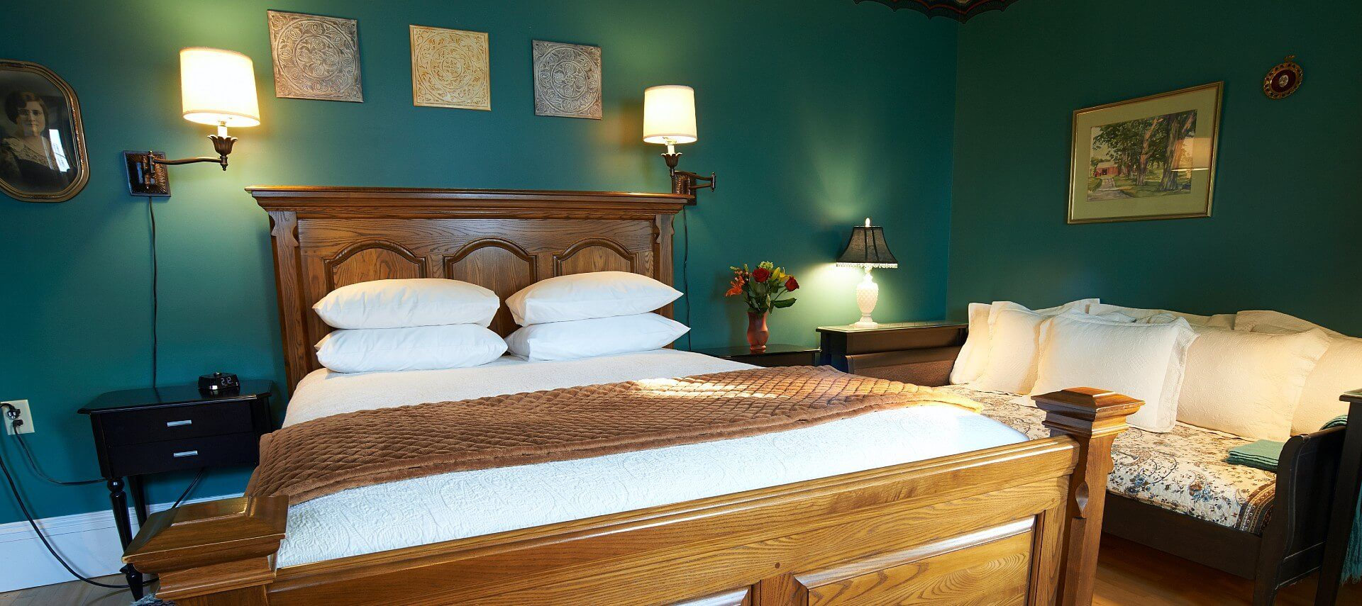 Bedroom with green walls, queen bed with large wooden headboard and footboard, day bed and paintings on the walls.