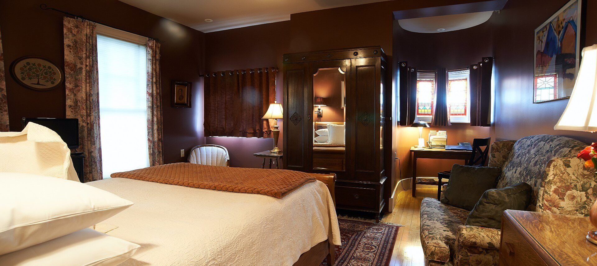 Large bedroom showing bed with white linens, dark brown walls, upholstered chair, sitting desk and large armoire.