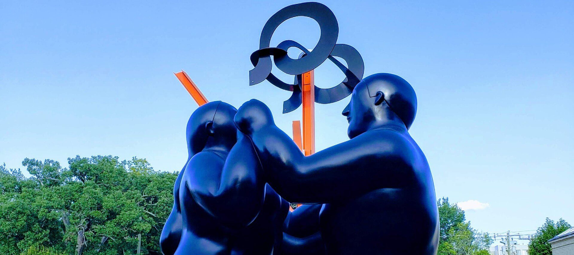 Large artistic sculpture depicting two people facing each other holding hands with orange spikes and circular designs above.