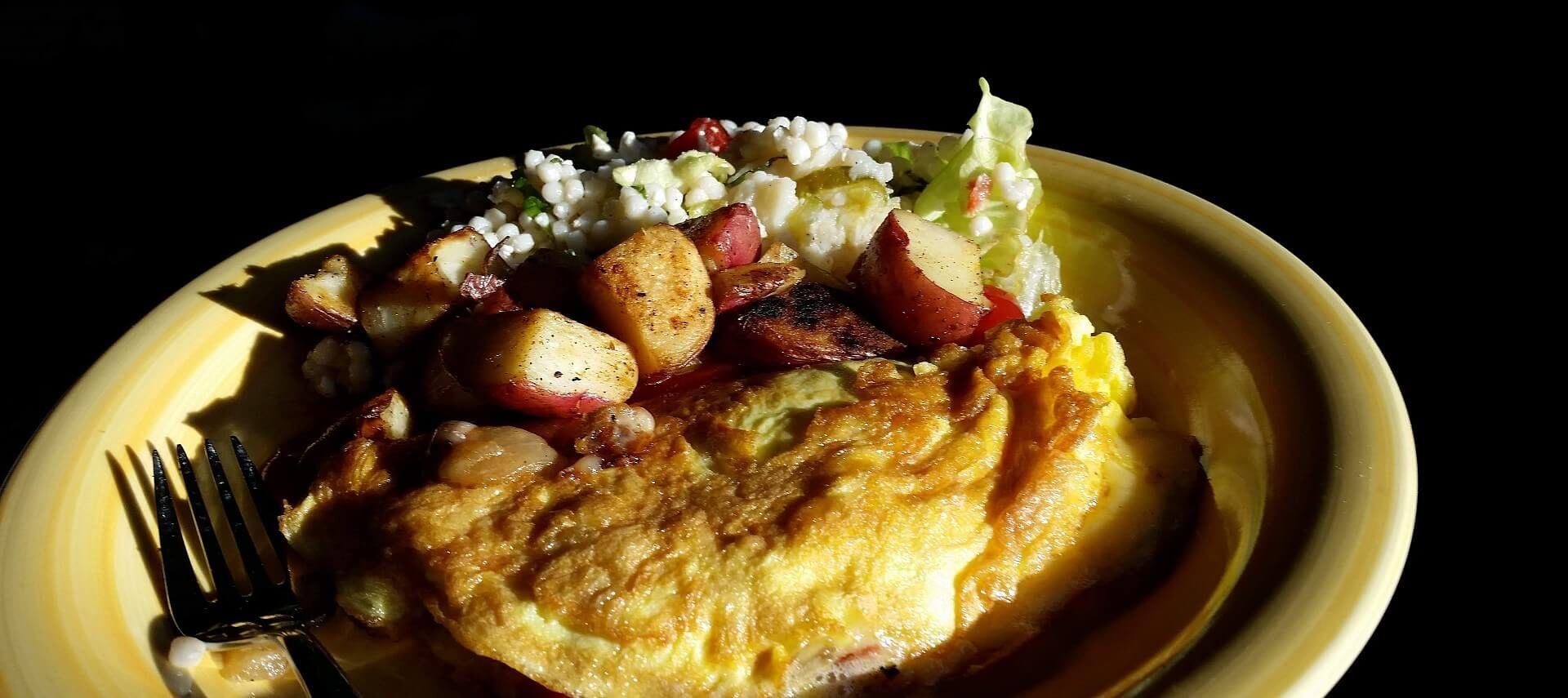 Yellow plate against a dark black background showing an omelette, diced redskin potatoes and silver fork.