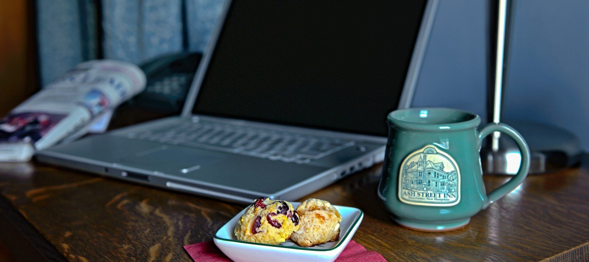 Brown desk with small plate of scones, green ceramic mug and an open silver laptop.