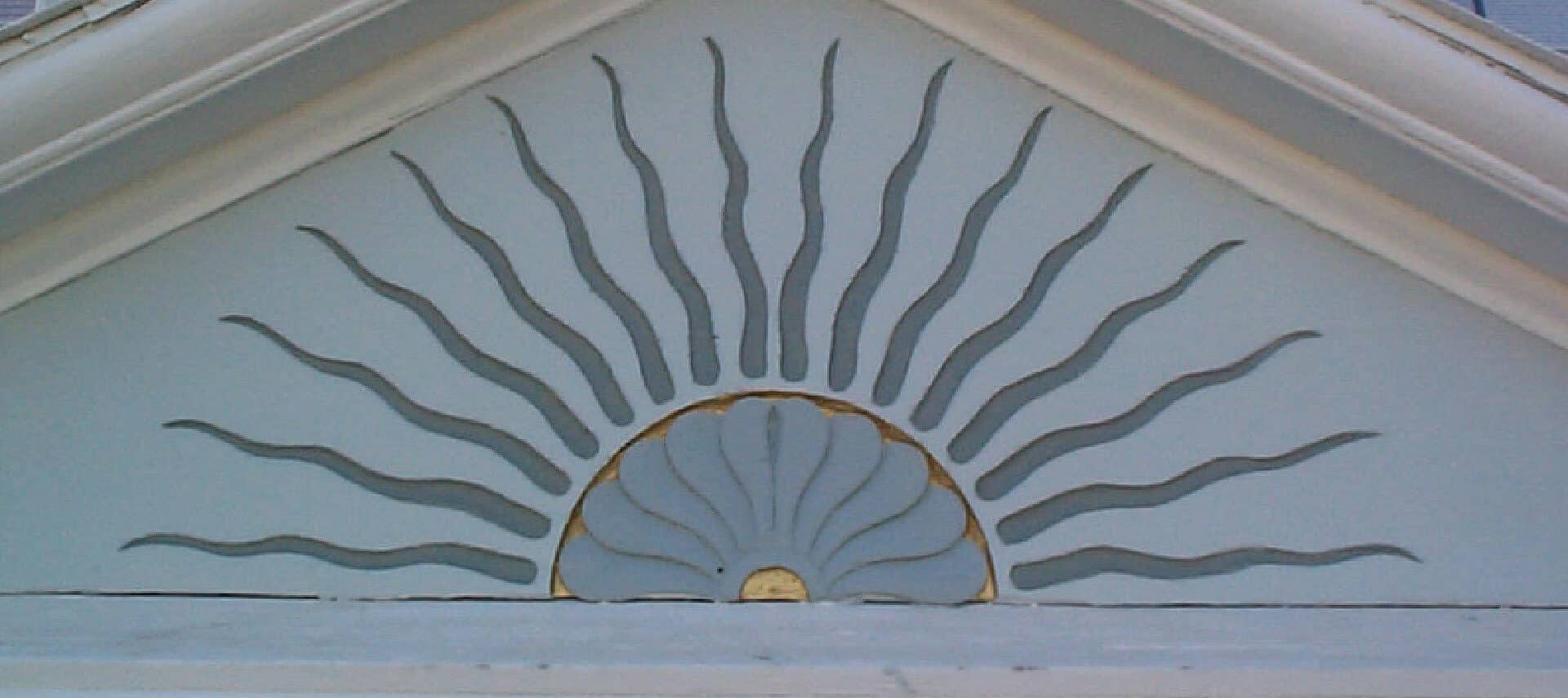 Top peak of the front of a home showing a grey sunburst pattern