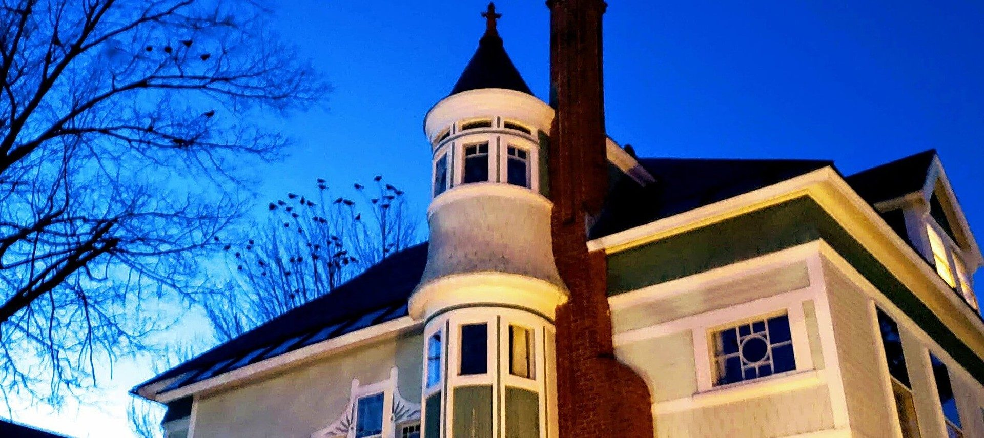 Top corner view of a home featuring red brick fireplace and dome with spire top against a blue sky at dusk