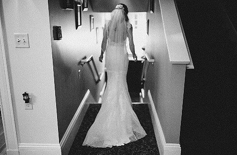 Backside of a bride wearing a white dress in veil standing in a hallway about to walk down a set of stairs.