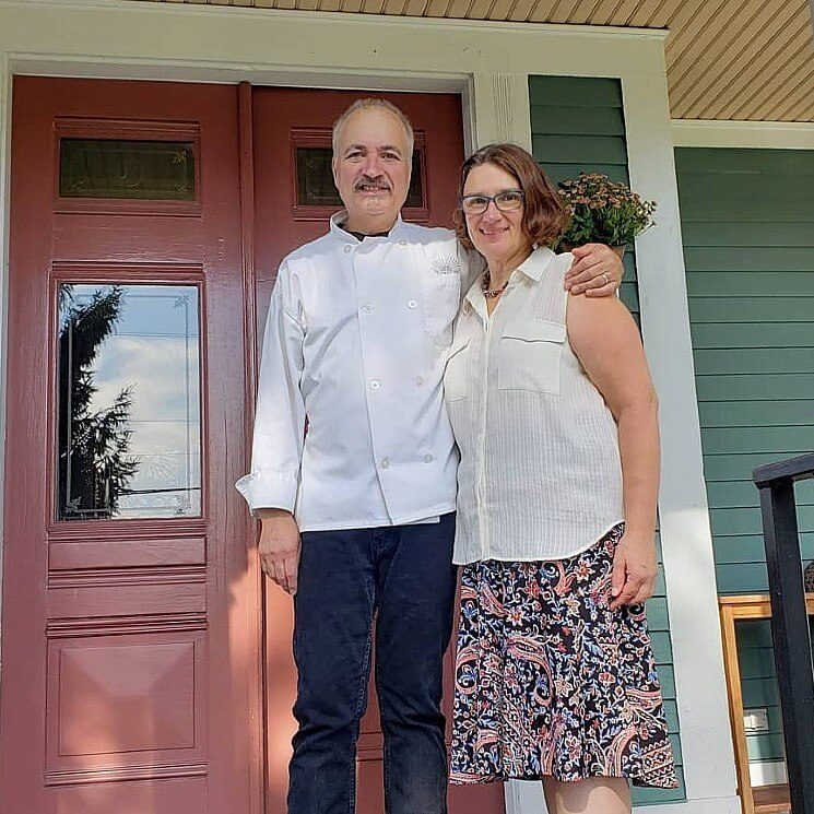 A woman in a white dressy tank top and floral skirt standing next to a man with jeans and white chef's coat at the front door of a home.