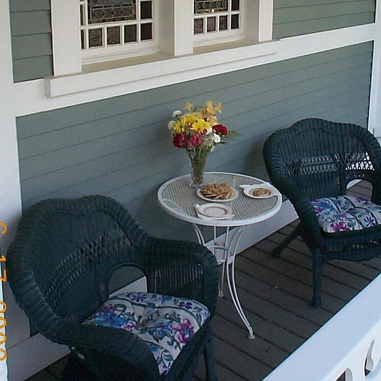 Two dark blue wicker chairs with floral cushions on a porch with a white side table holding flowers and snacks.