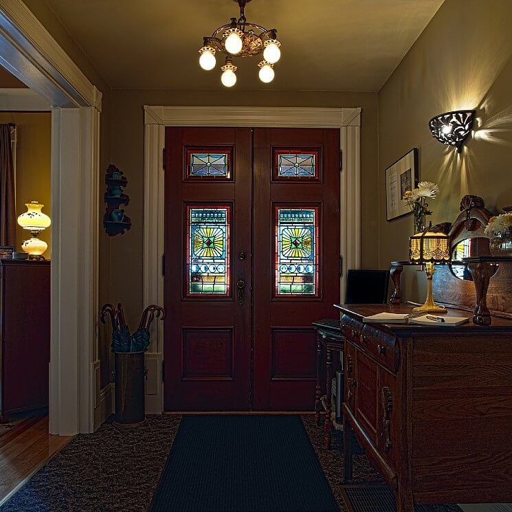 Large dark brown front doors with stained glass windows and the foyer of a home with antique furniture.