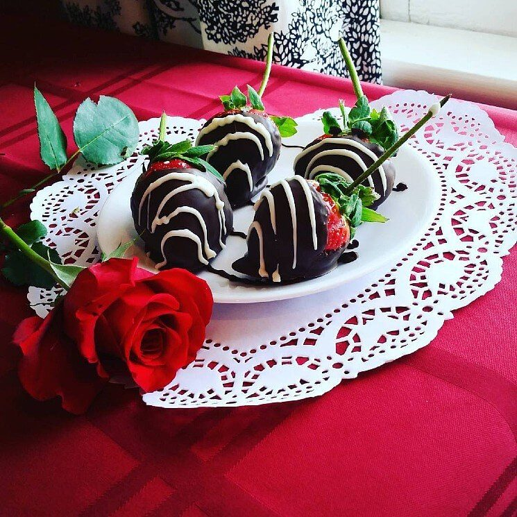 Table with red table cloth and lace doily holding a red plate with chocolate covered strawberries and one red rose.